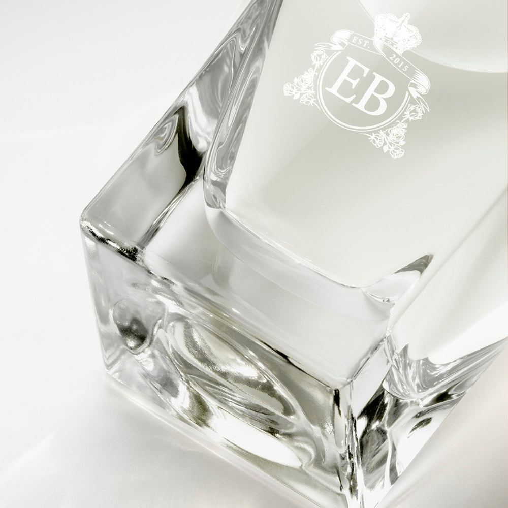 Detail of the bottom of the 100 ml bottle, with transparent glass and yellowish perfum. Detail of logo with the EB initials in white ink. Kingston Osmanthus, a fragrance by Eric Butherbaugh.