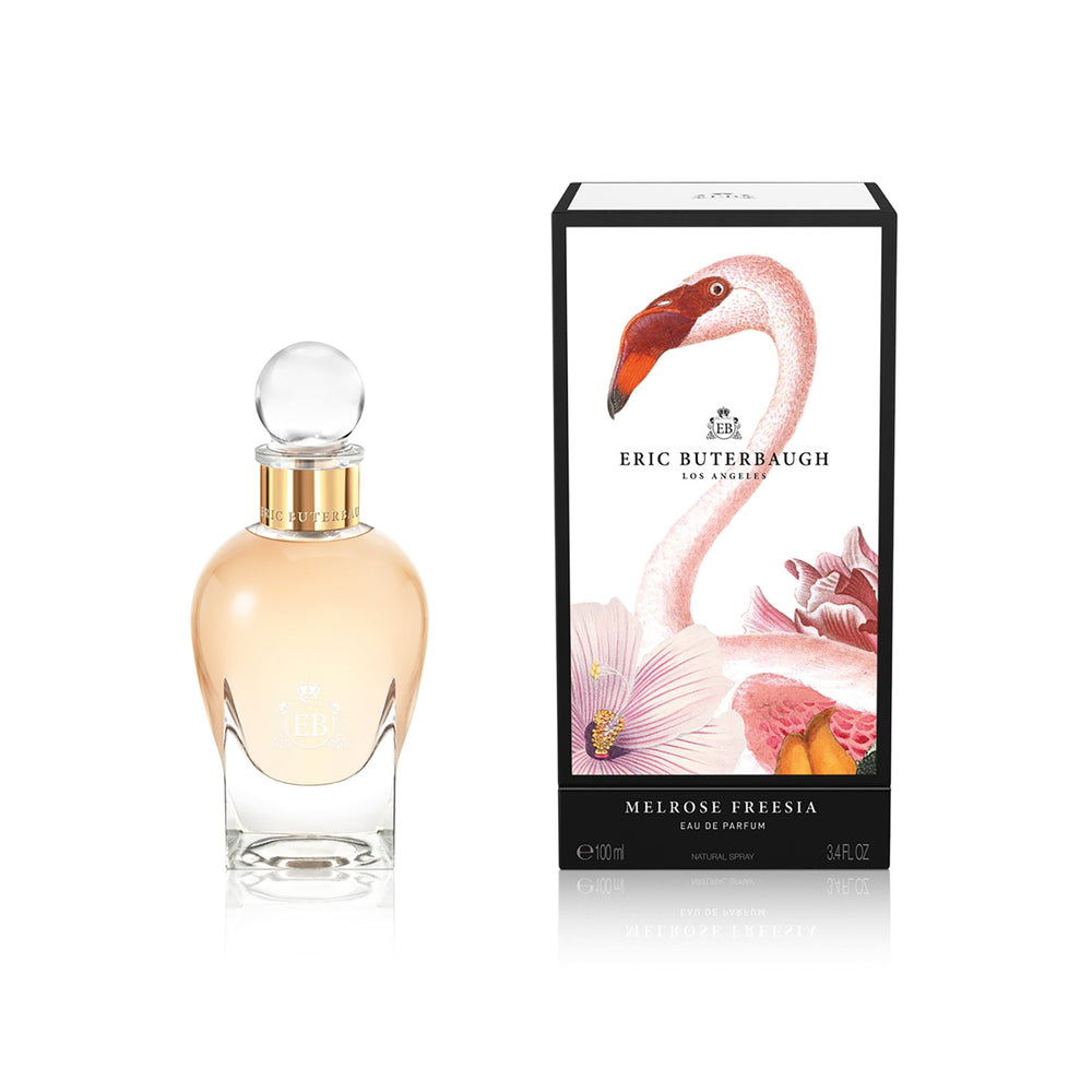 100 ml bottle, with transparent glass and orangey perfum. Spherical cap with gold band. By his side the box, with pink flamingo and flowers illustration, within a black border. Melrose Fresia, a fragrance by Eric Butherbaugh.