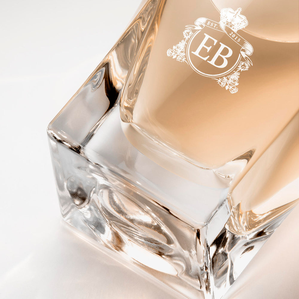 Detail of the bottom of the 100 ml bottle, with transparent glass and orangey perfum. Detail of logo with the EB initials in white ink. Melrose Fresia, a fragrance by Eric Butherbaugh.