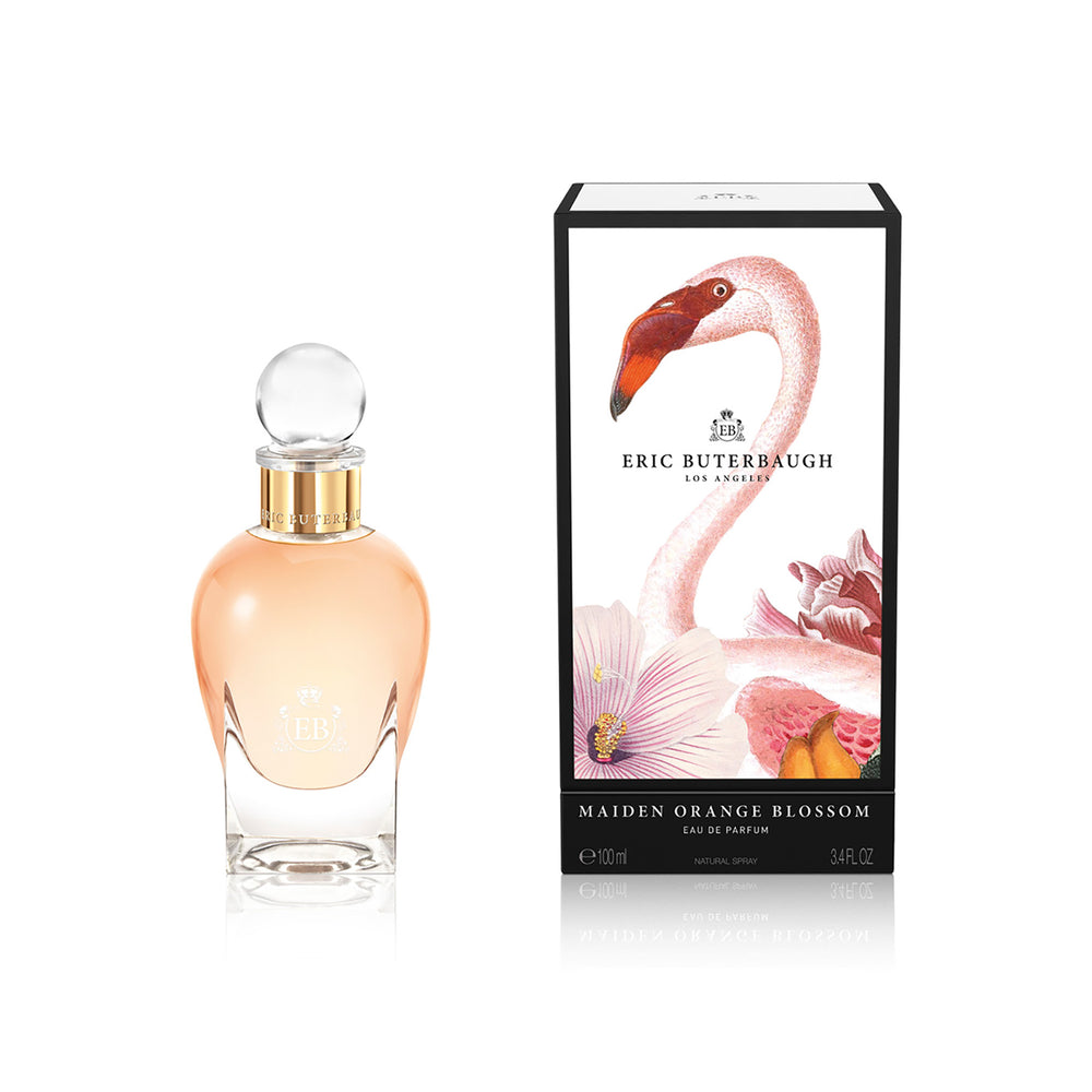 100 ml bottle, with transparent glass and orangey perfum. Spherical cap with gold band. By his side the box, with pink flamingo and flowers illustration, within a black border. Maiden Orange Blossom, a fragrance by Eric Butherbaugh.