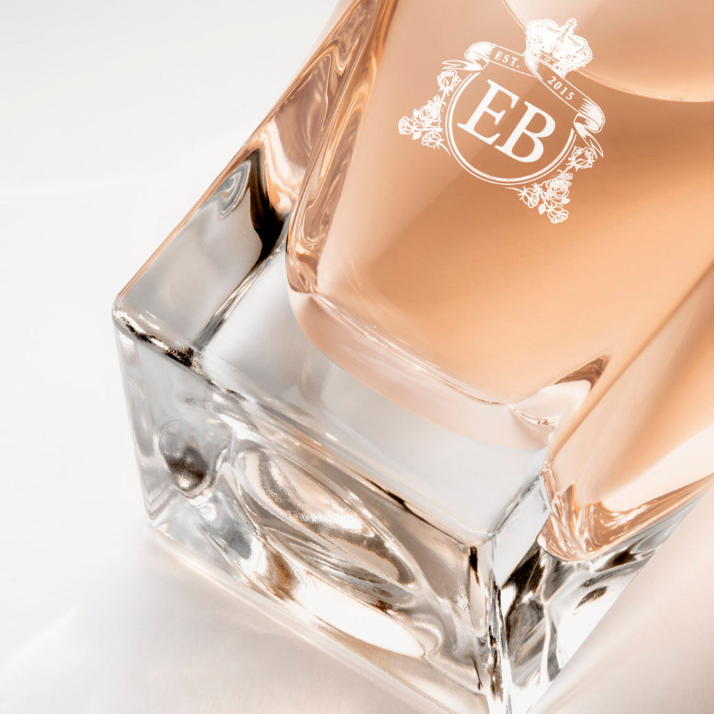 Detail of the bottom of the 100 ml bottle, with transparent glass and orangey perfum. Detail of logo with the EB initials in white ink. Maiden Orange Blossom, a fragrance by Eric Butherbaugh.