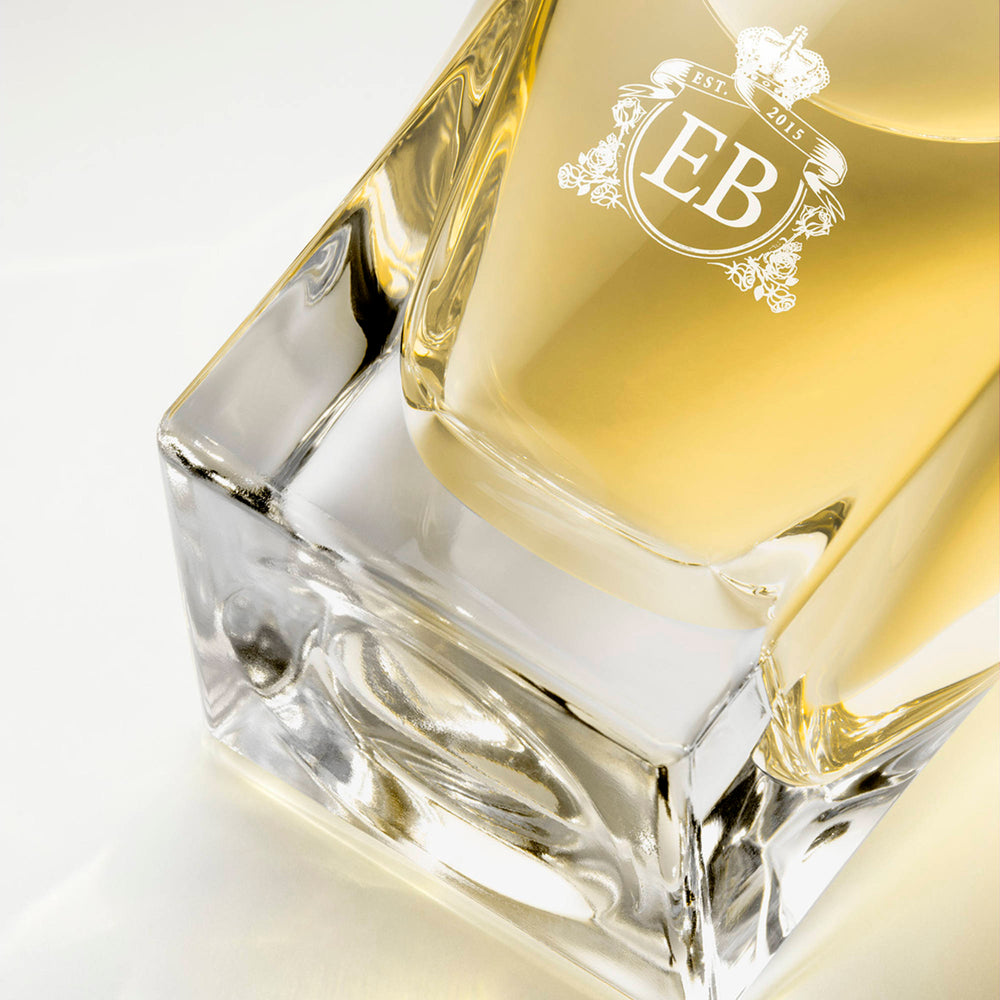 Detail of the bottom of the 100 ml bottle, with transparent glass and yellowish perfum. Detail of logo with the EB initials in white ink. Nick´s Sunflower, a fragrance by Eric Butherbaugh.