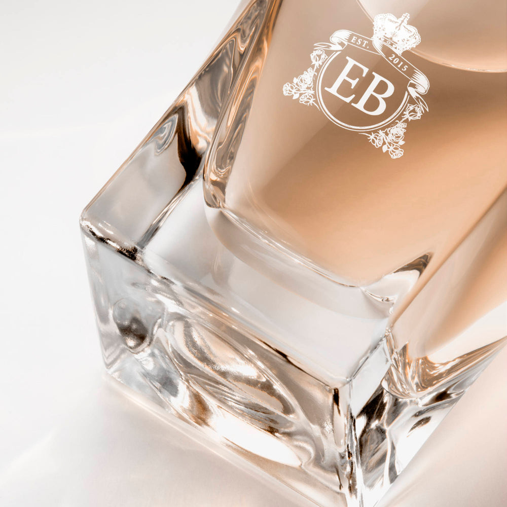 Detail of the bottom of the 100 ml bottle, with transparent glass and orangey perfum. Detail of logo with the EB initials in white ink. Regal Tuberose, a fragrance by Eric Butherbaugh.