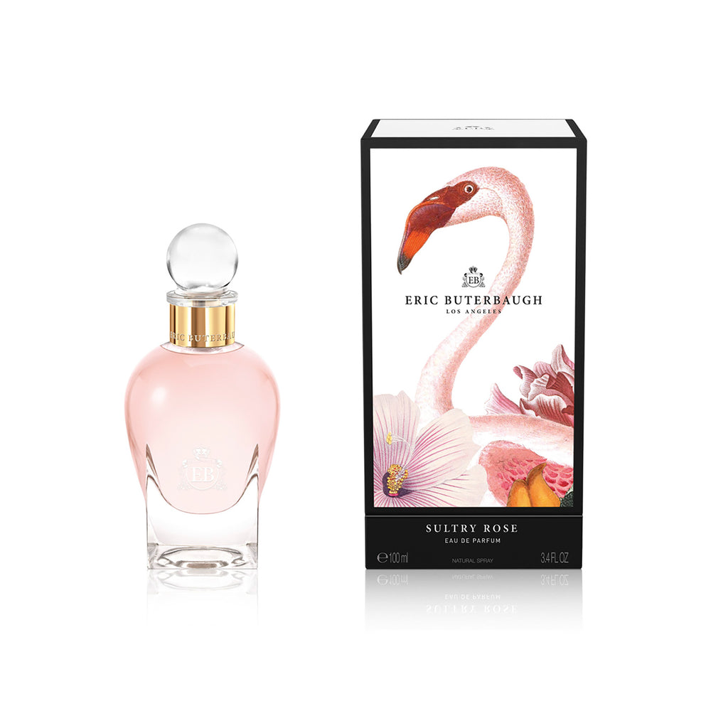 100 ml bottle, with transparent glass and pinkish perfum. Spherical cap with gold band. By his side the box, with pink flamingo and flowers illustration, within a black border. Sultry Rose, a fragrance by Eric Butherbaugh.