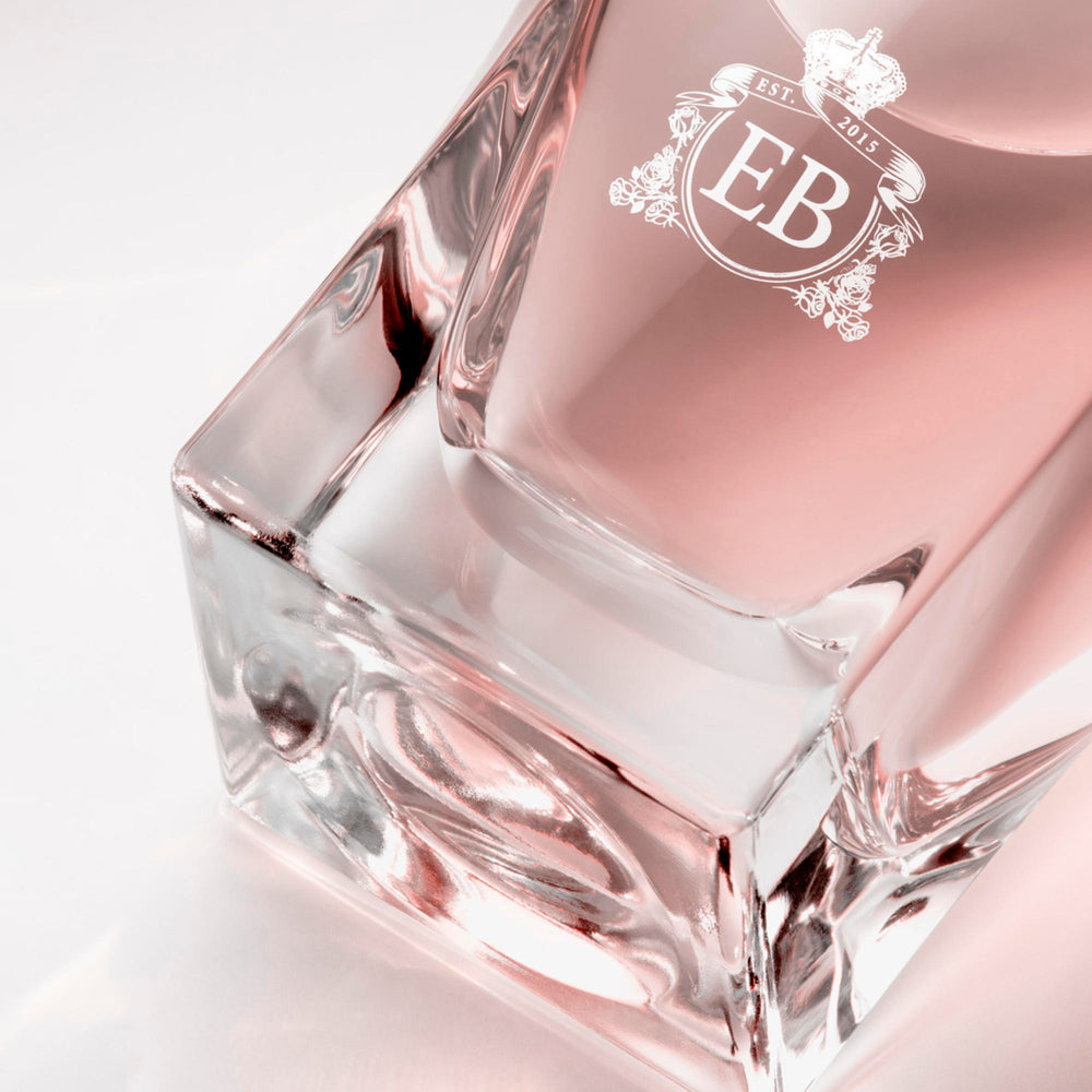 Detail of the bottom of the 100 ml bottle, with transparent glass and pinkish perfum. Detail of logo with the EB initials in white ink. Sultry Rose, a fragrance by Eric Butherbaugh.