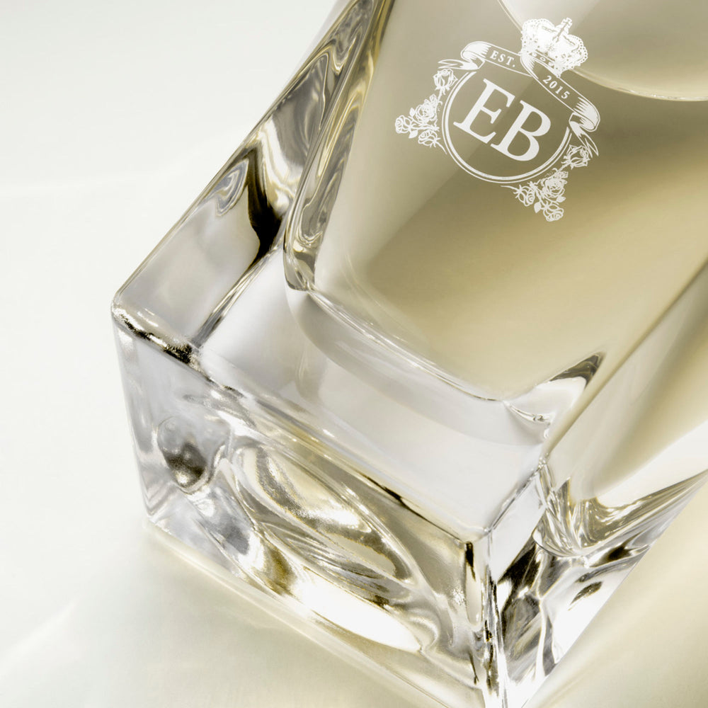 Detail of the bottom of the 100 ml bottle, with transparent glass and yellowish perfum. Detail of logo with the EB initials in white ink. Virgin Lily of the Valley, a fragrance by Eric Butherbaugh.