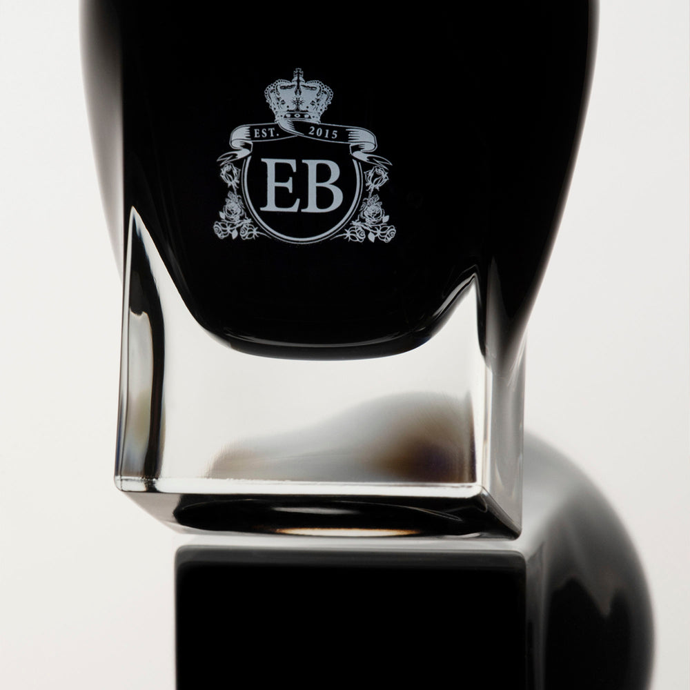 Detail of the bottom of the 100 ml bottle, with black opaque glass. Detail of logo with the EB initials in white ink. Oud Rose, a fragrance by Eric Butherbaugh.