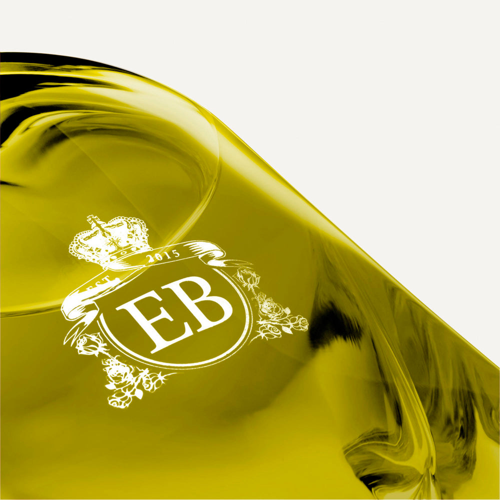 Detail of the bottom of the 250 ml bottle, with transparent glass and greenish perfum. Detail of logo with the EB initials in white ink. Apollo Hyacinth, a fragrance by Eric Butherbaugh.