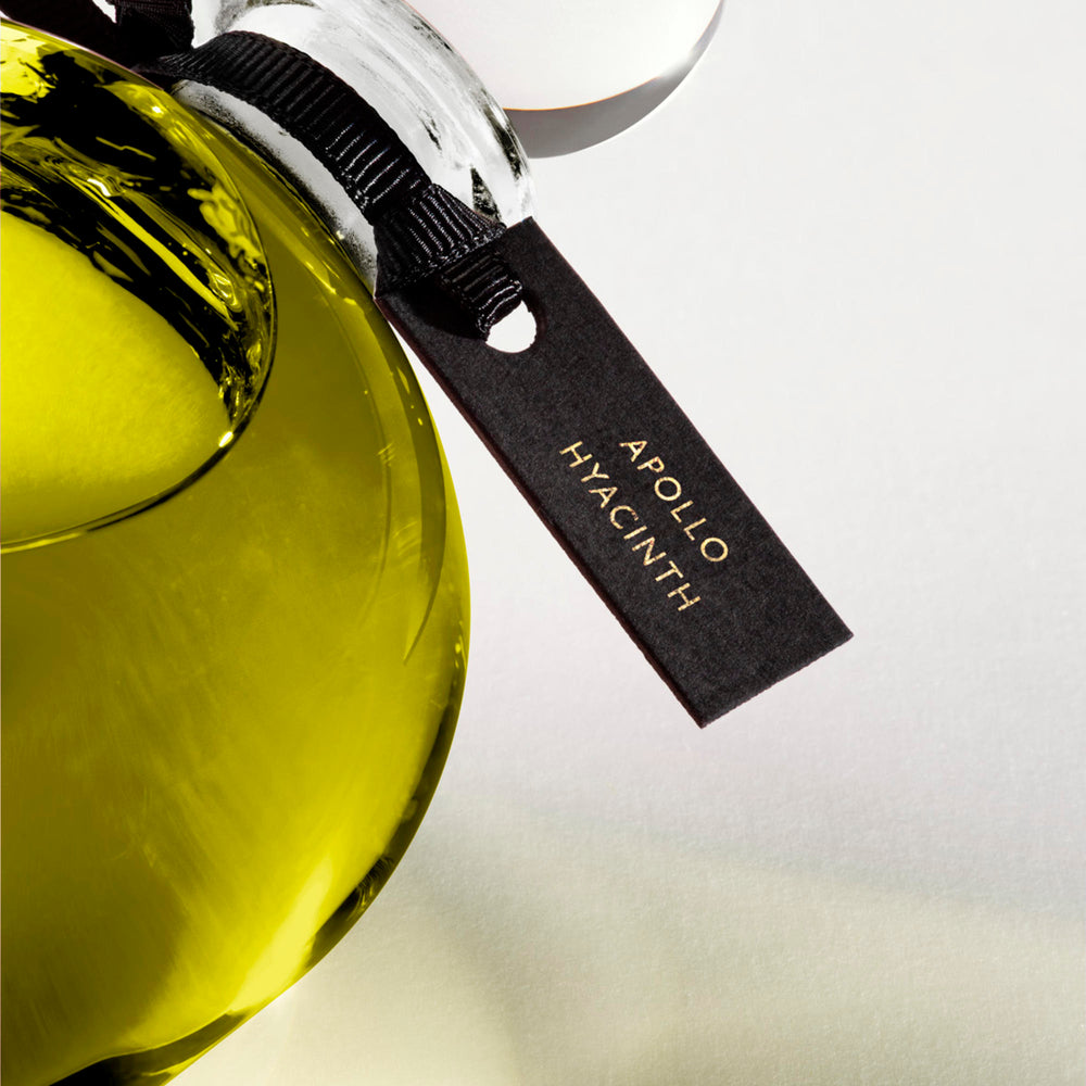 Detail of the top of the 250 ml bottle, with transparent glass and greenish perfum. Spherical cap with black ribbon. Apollo Hyacinth, a fragrance by Eric Butherbaugh.