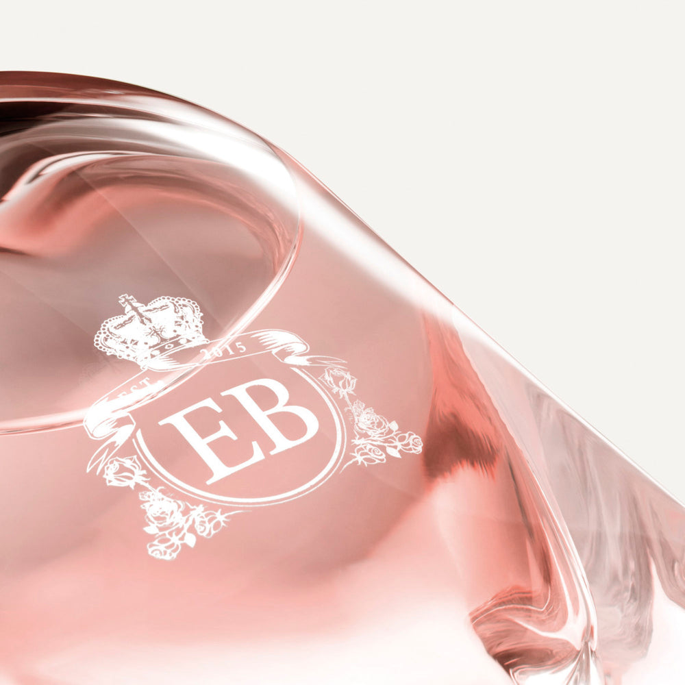 Detail of the bottom of the 250 ml bottle, with transparent glass and pinkish perfum. Detail of logo with the EB initials in white ink. Celestial Jasmine, a fragrance by Eric Butherbaugh.