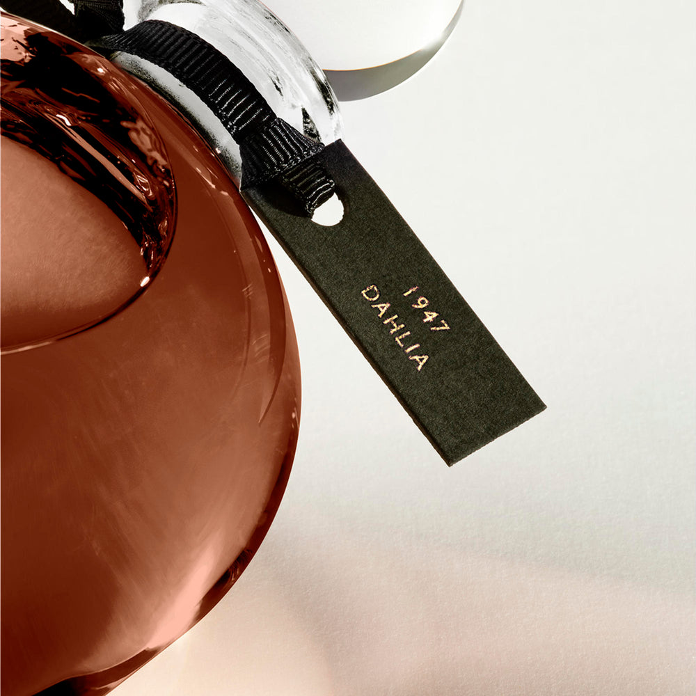 Detail of the top of the 250 ml bottle, with transparent glass and amber perfum. Spherical cap with black ribbon. 1947 Dalhia, a fragrance by Eric Butherbaugh.