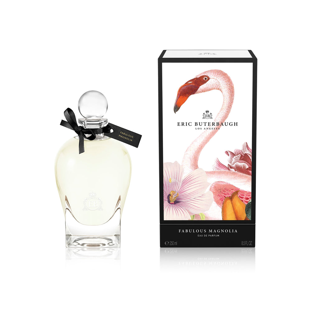 250 ml bottle, with transparent glass and yellowish perfum. Spherical cap with black ribbon. By his side the box, with pink flamingo and flowers illustration, within a black border. Fabulous Magnolia, a fragrance by Eric Butherbaugh.