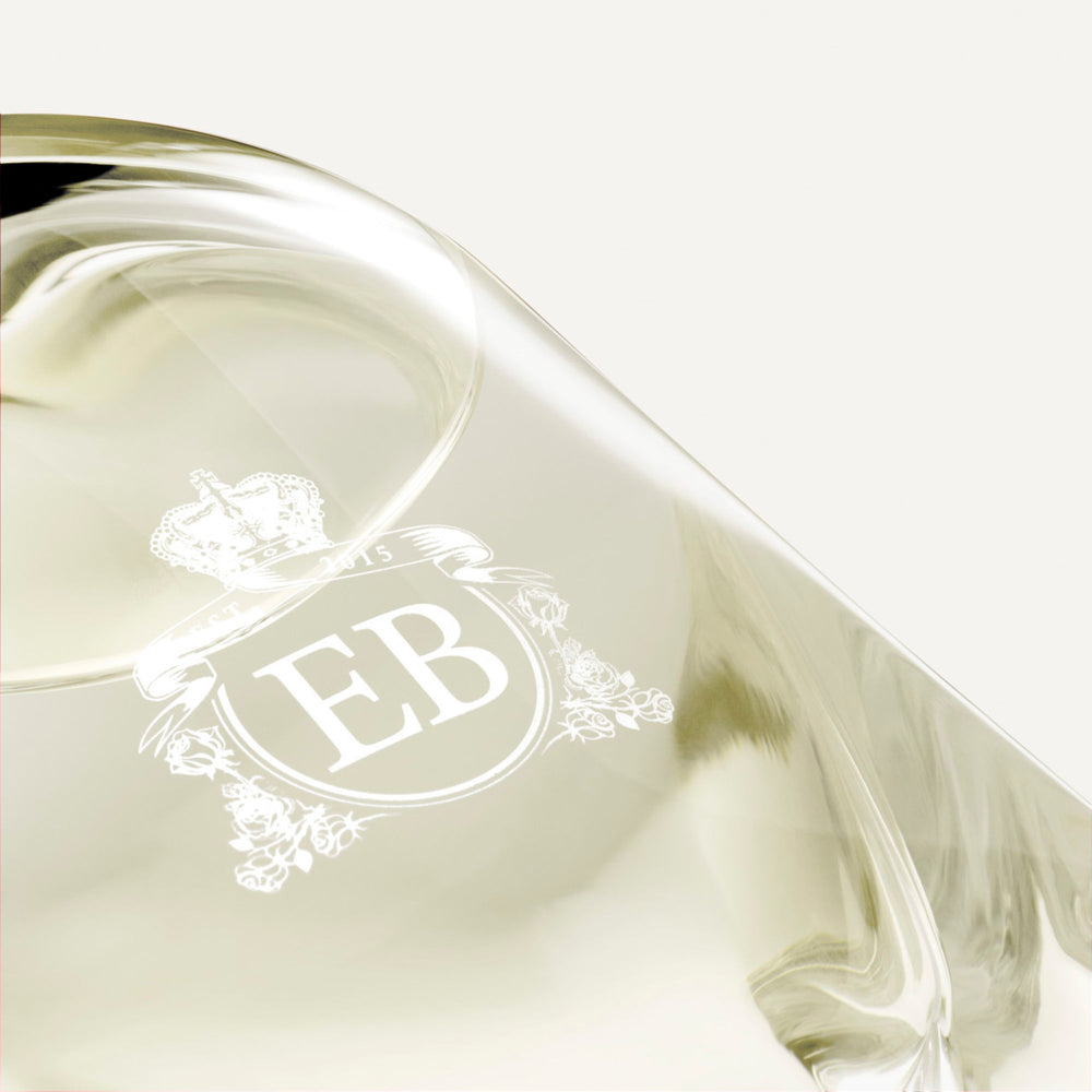Detail of the bottom of the 250 ml bottle, with transparent glass and yellowish perfum. Detail of logo with the EB initials in white ink. Fabulous Magnolia, a fragrance by Eric Butherbaugh.