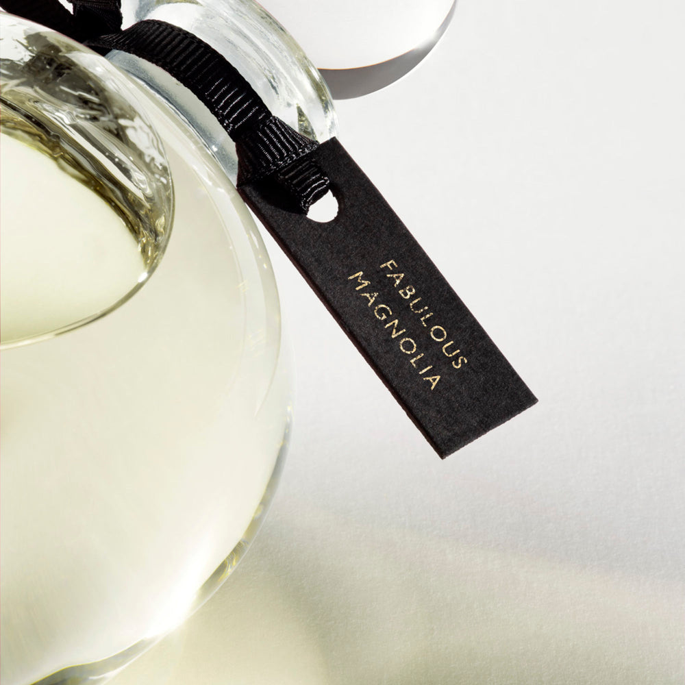 Detail of the top of the 250 ml bottle, with transparent glass and yellowish perfum. Spherical cap with black ribbon. Fabulous Magnolia, a fragrance by Eric Butherbaugh.