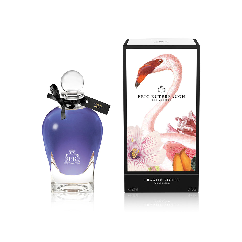 250 ml bottle, with transparent glass and violet perfum. Spherical cap with black ribbon. By his side the box, with pink flamingo and flowers illustration, within a black border. Fragile Violet, a fragrance by Eric Butherbaugh.