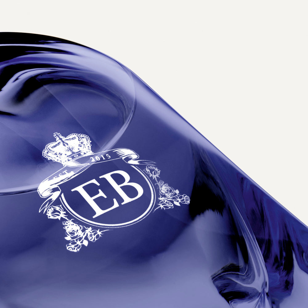 Detail of the bottom of the 250 ml bottle, with transparent glass and violet perfum. Detail of logo with the EB initials in white ink. Fragile Violet, a fragrance by Eric Butherbaugh.