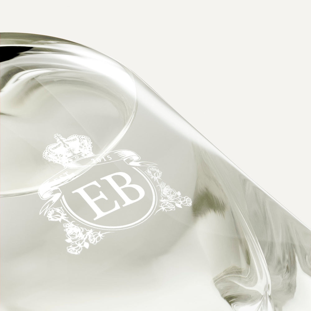 Detail of the bottom of the 250 ml bottle, with transparent glass and yellowish perfum. Detail of logo with the EB initials in white ink. Kingston Osmanthus, a fragrance by Eric Butherbaugh.