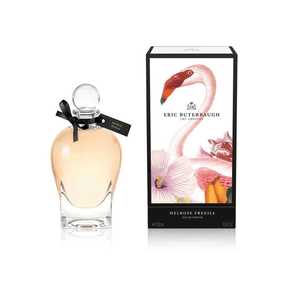 250 ml bottle, with transparent glass and orangey perfum. Spherical cap with black ribbon. By his side the box, with pink flamingo and flowers illustration, within a black border. Melrose Fresia, a fragrance by Eric Butherbaugh.