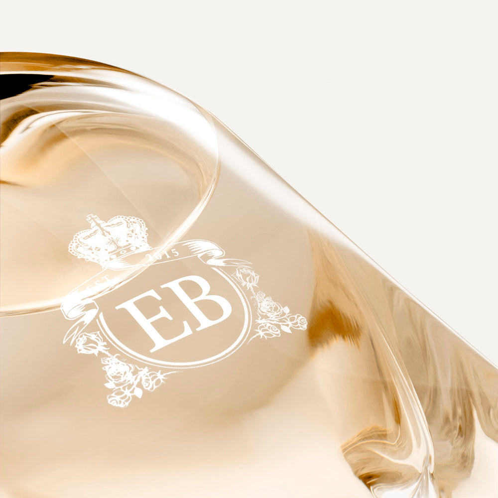 Detail of the bottom of the 250 ml bottle, with transparent glass and orangey perfum. Detail of logo with the EB initials in white ink. Melrose Fresia, a fragrance by Eric Butherbaugh.