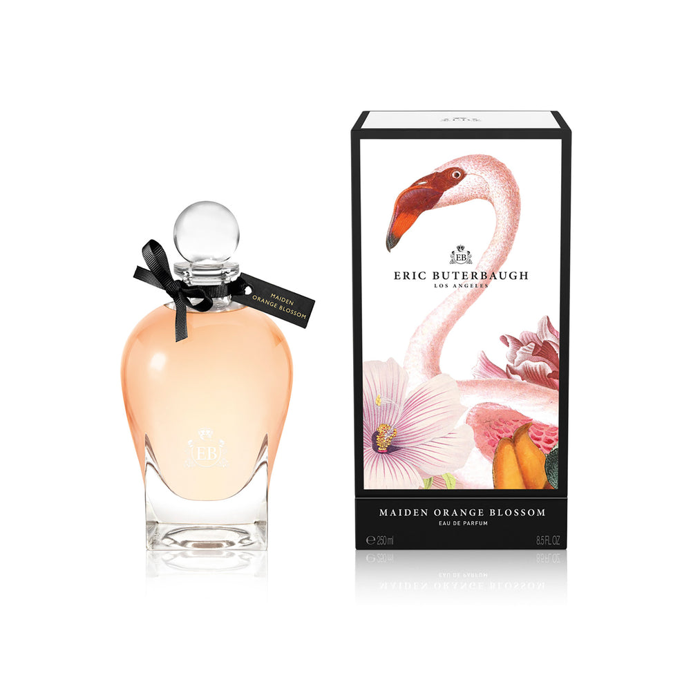 250 ml bottle, with transparent glass and orangey perfum. Spherical cap with black ribbon. By his side the box, with pink flamingo and flowers illustration, within a black border. Maiden Orange Blossom, a fragrance by Eric Butherbaugh.