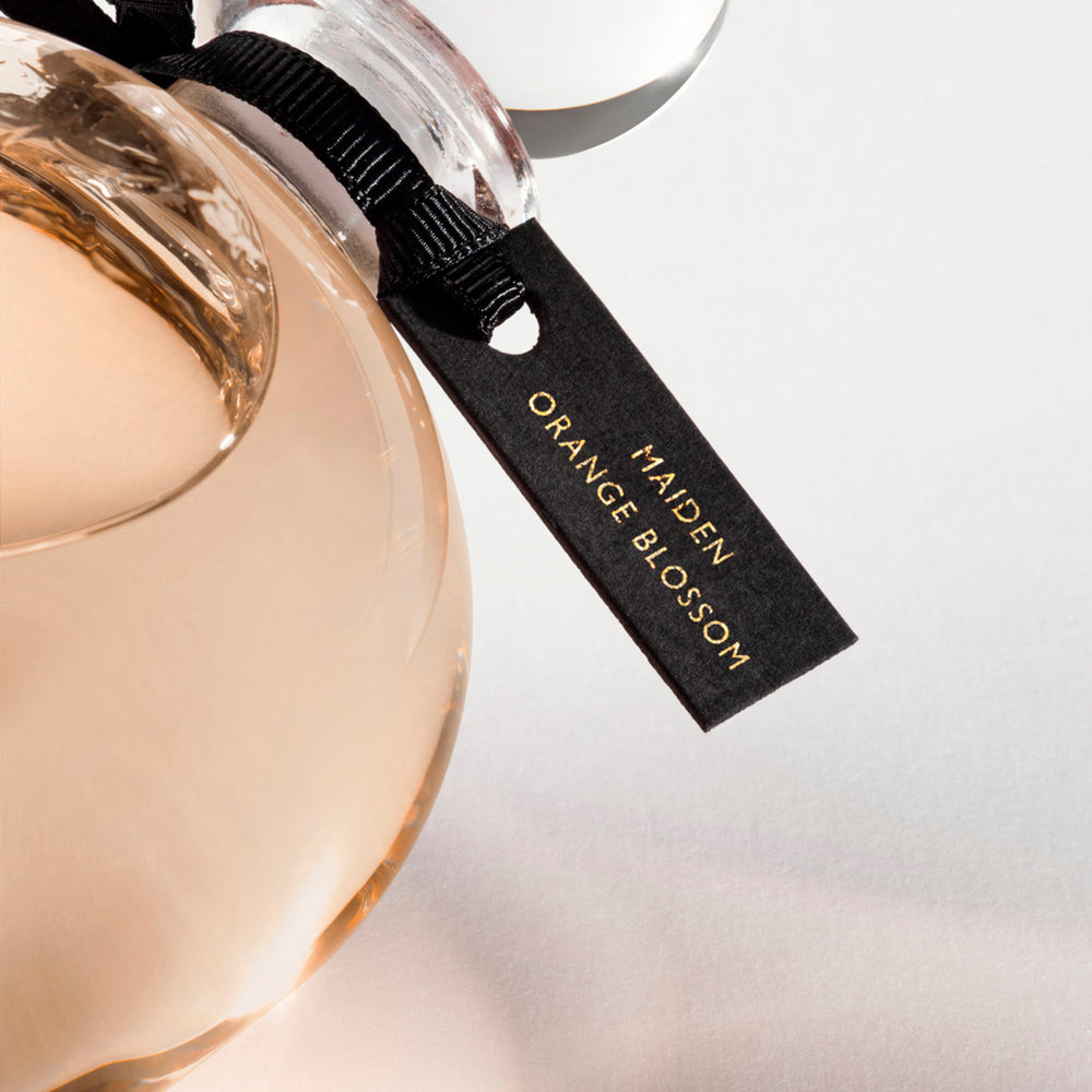 Detail of the top of the 250 ml bottle, with transparent glass and orangey perfum. Spherical cap with black ribbon. Maiden Orange Blossom, a fragrance by Eric Butherbaugh.