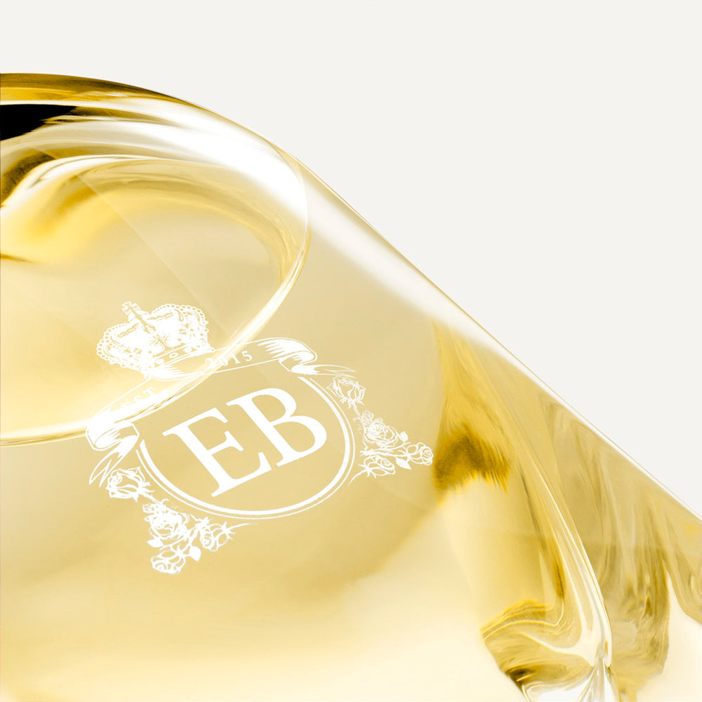 Detail of the bottom of the 250 ml bottle, with transparent glass and yellowish perfum. Detail of logo with the EB initials in white ink. Nick´s Sunflower, a fragrance by Eric Butherbaugh.