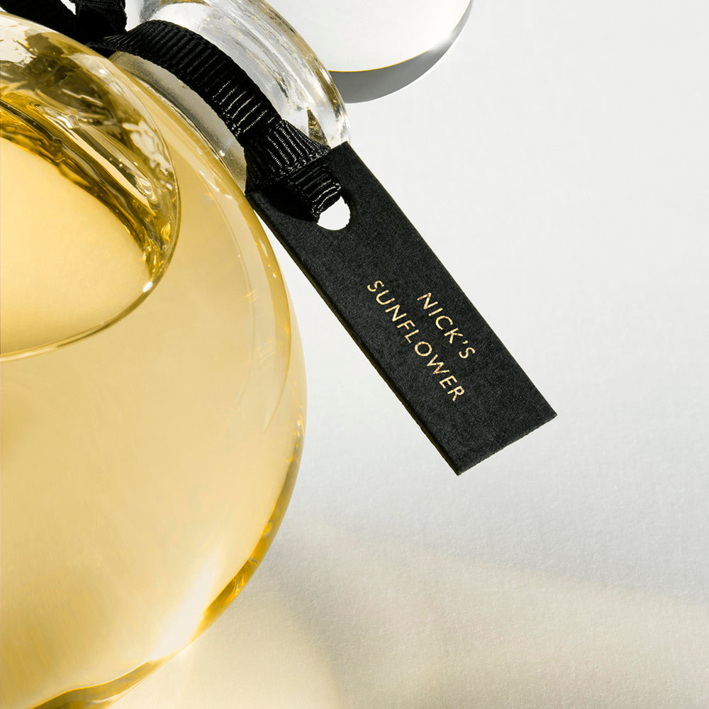 Detail of the top of the 250 ml bottle, with transparent glass and yellowish perfum. Spherical cap with black ribbon. Nick´s Sunflower, a fragrance by Eric Butherbaugh.