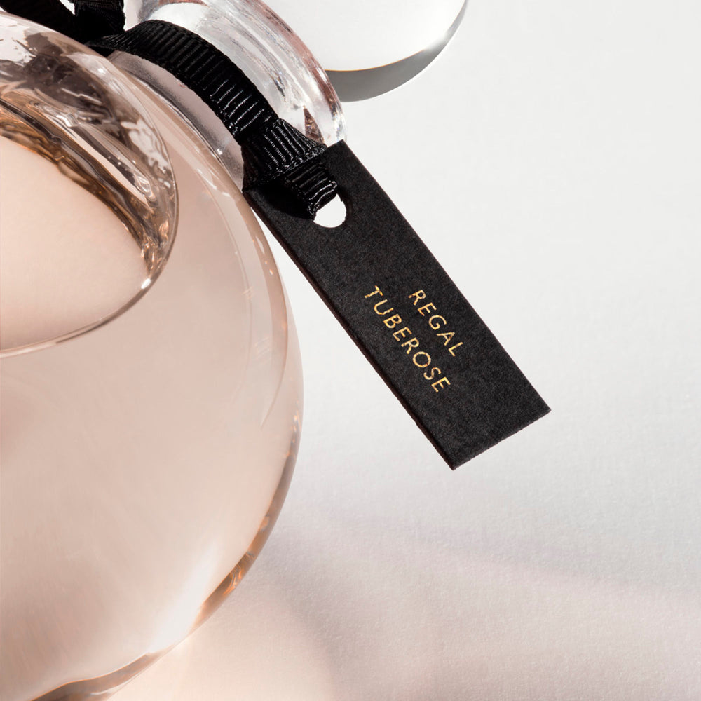 Detail of the top of the 250 ml bottle, with transparent glass and orangey perfum. Spherical cap with black ribbon. Regal Tuberose, a fragrance by Eric Butherbaugh.
