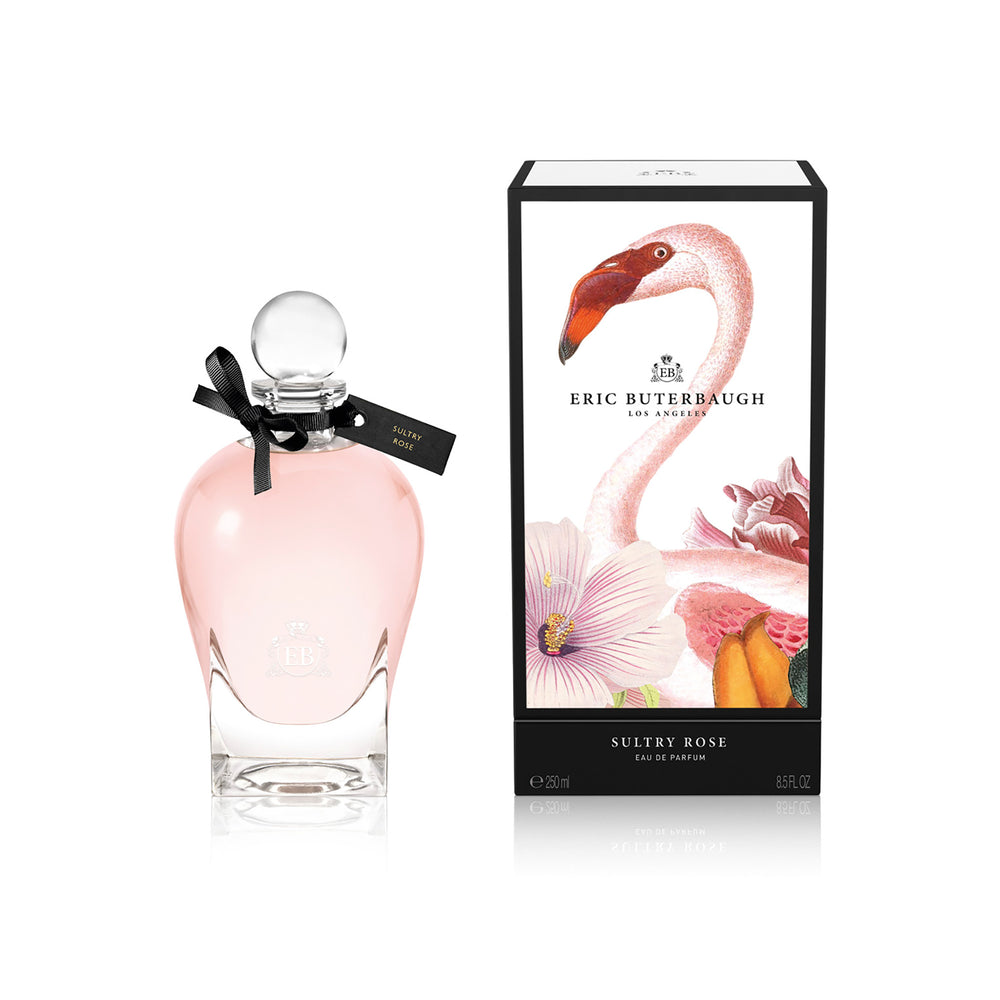 250 ml bottle, with transparent glass and pinkish perfum. Spherical cap with black ribbon. By his side the box, with pink flamingo and flowers illustration, within a black border. Sultry Rose, a fragrance by Eric Butherbaugh.
