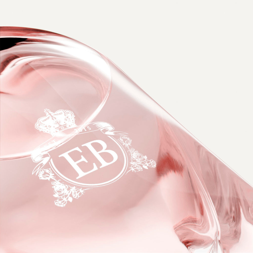 Detail of the bottom of the 250 ml bottle, with transparent glass and pinkish perfum. Detail of logo with the EB initials in white ink. Sultry Rose, a fragrance by Eric Butherbaugh.
