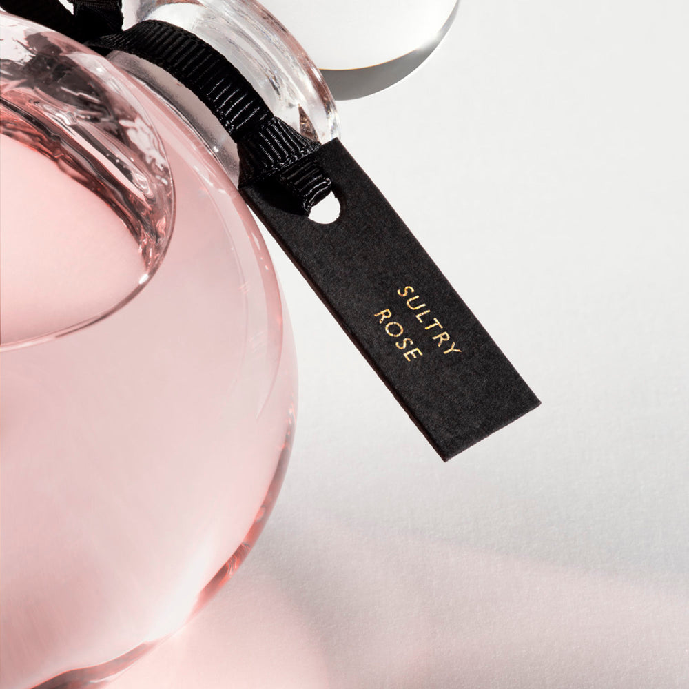 Detail of the top of the 250 ml bottle, with transparent glass and pinkish perfum. Spherical cap with black ribbon. Sultry Rose, a fragrance by Eric Butherbaugh.
