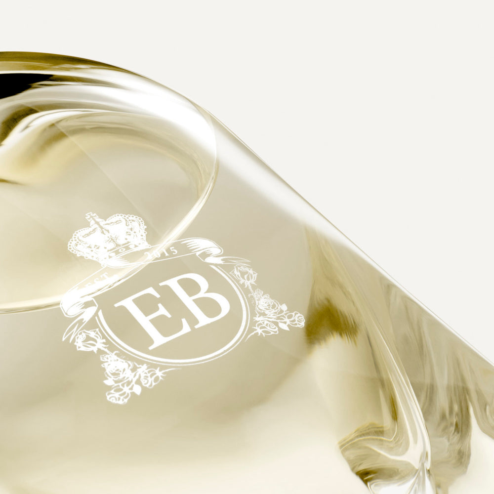 Detail of the bottom of the 250 ml bottle, with transparent glass and yellowish perfum. Detail of logo with the EB initials in white ink. Virgin Lily of the Valley, a fragrance by Eric Butherbaugh.