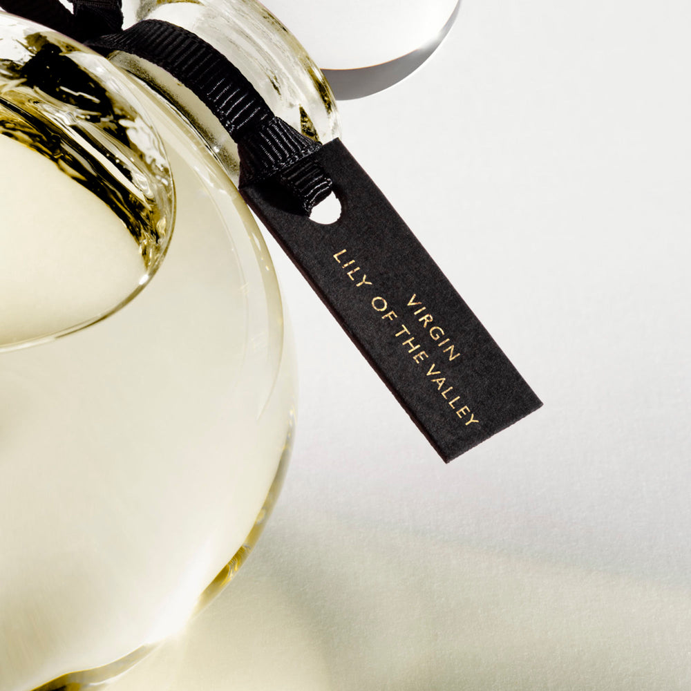 Detail of the top of the 250 ml bottle, with transparent glass and yellowish perfum. Spherical cap with black ribbon. Virgin Lily of the Valley, a fragrance by Eric Butherbaugh.