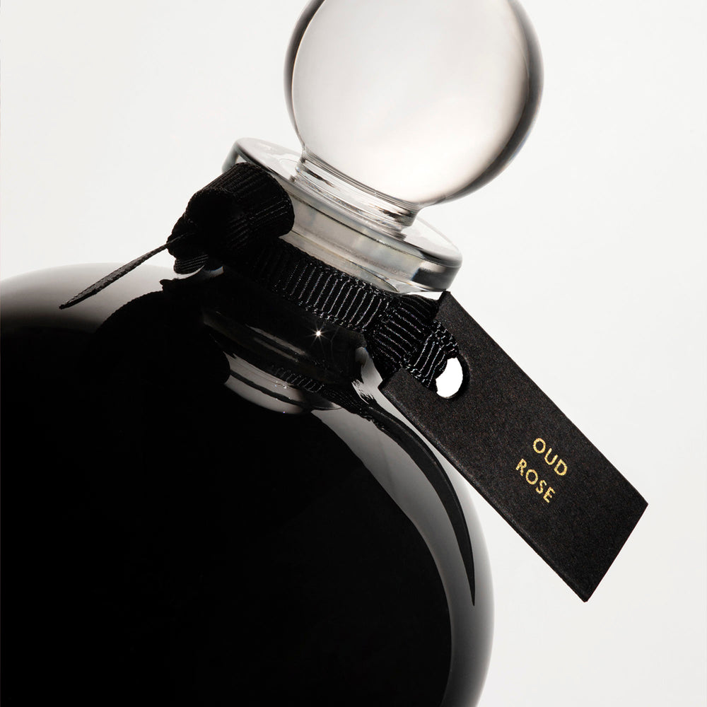 Detail of the top of the 250 ml bottle, with black opaque glass. Spherical cap with black ribbon. Oud Rose, a fragrance by Eric Butherbaugh.