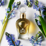 A 100 ml Apollo Hyacinth bottle lying next to some blue hyacinthus.