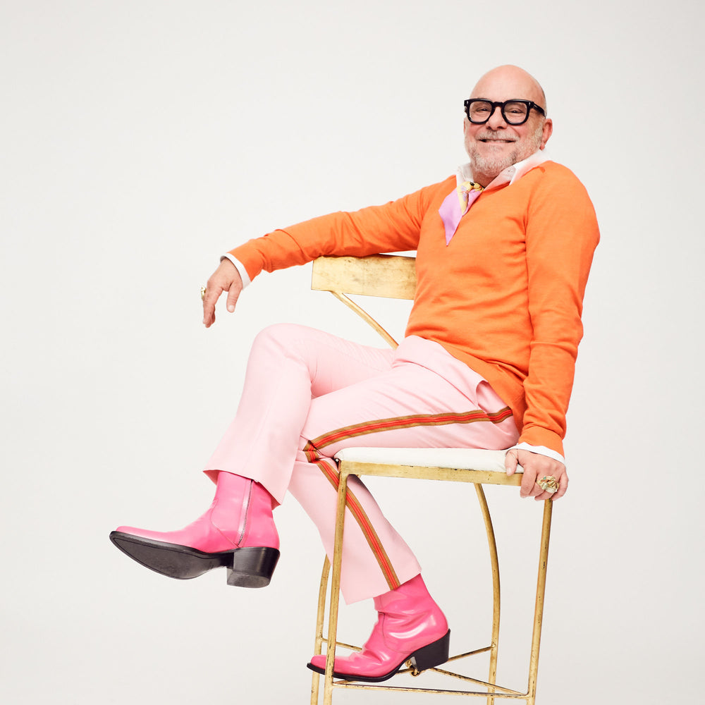 Eric Buterbaugh, dressed in color block, smiling sitting in a chair.