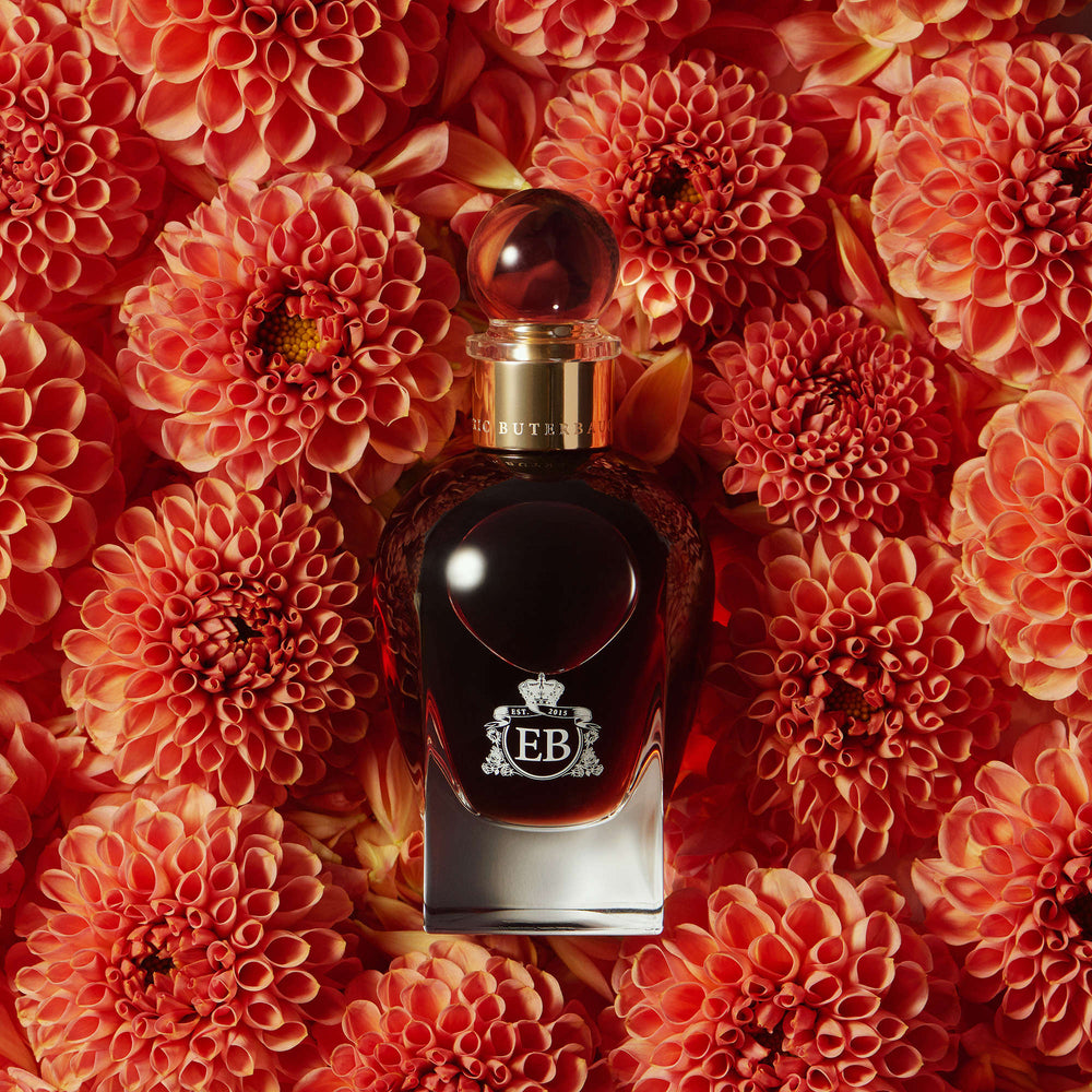 A 100 ml 1947 Dalhia bottle lying on a bed of orange dalhias.
