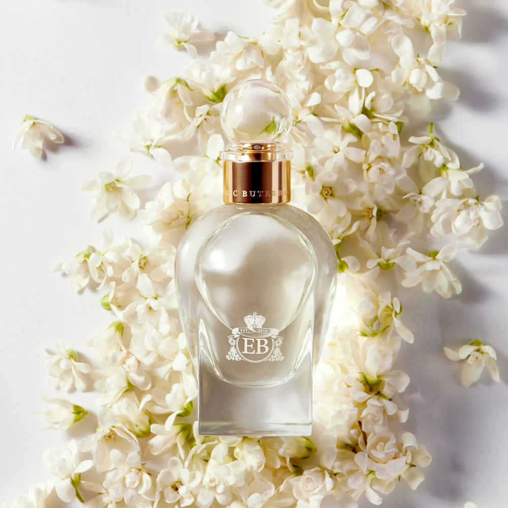 A 100 ml Kingston Osmanthus bottle lying on a bed of white osmanthus.
