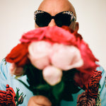 Eric Buterbaugh, with big sunglases, holding a pink roses bouquet.