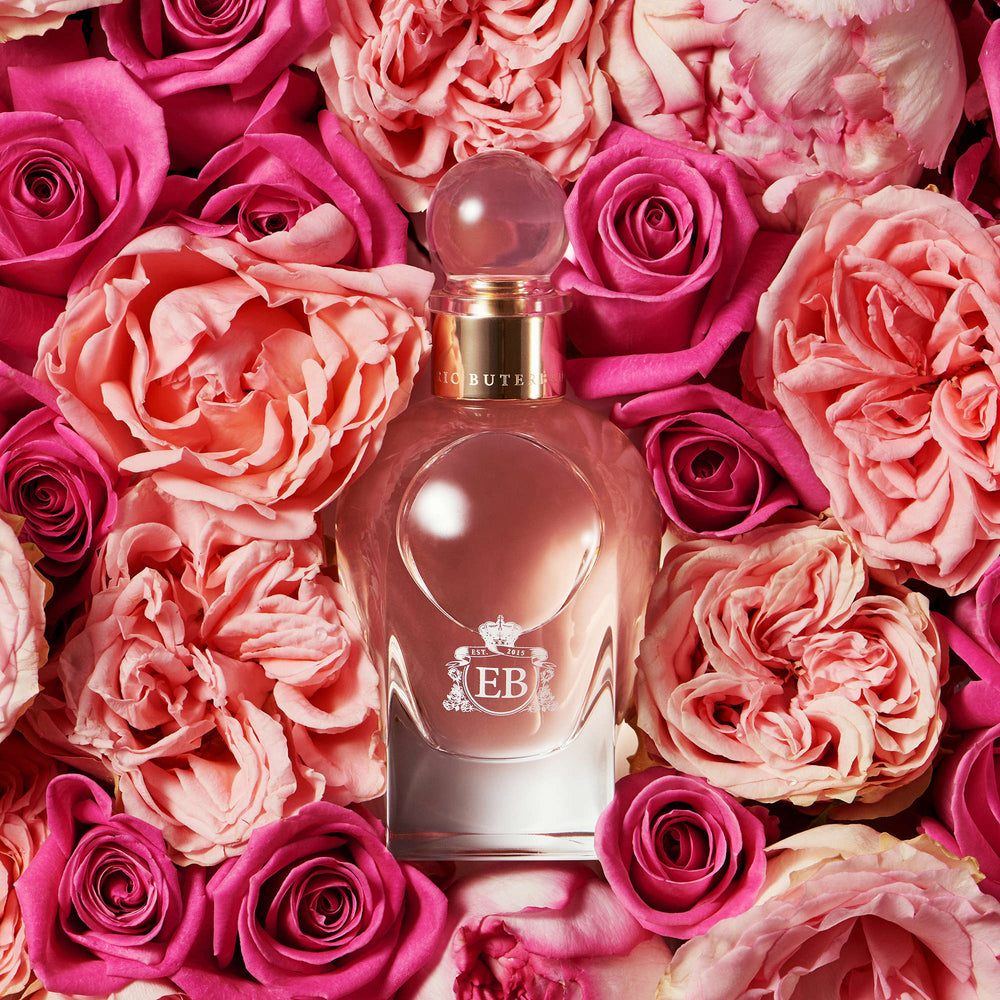 A 100 ml Sultry Rose bottle lying on a bed of pink roses.
