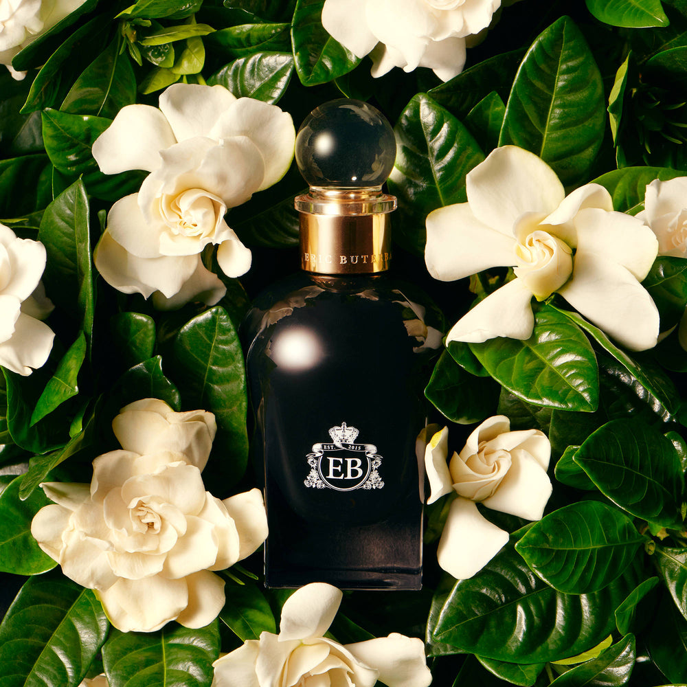A 100 ml Oud Gardenia bottle lying on a bed of gardenias.