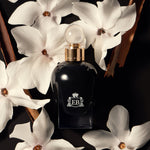 A 100 ml Oud Orange Flower bottle lying next to some orange blossoms.