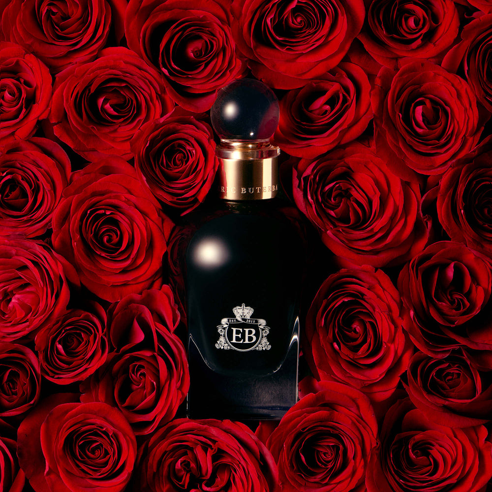 A 100 ml Oud Rose bottle lying on a bed of red roses.