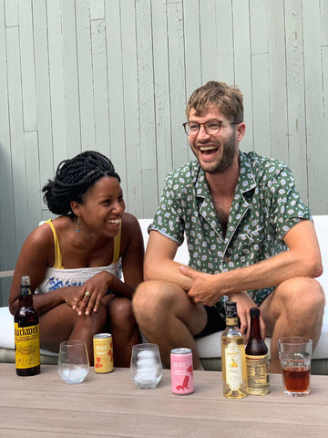 picture of Alex Doman and Denetrias Charlemagne Co-founders AVEC drinks laughing