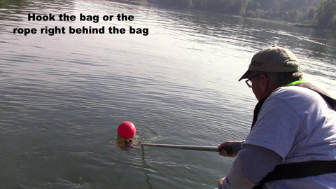 with your boat hook, hook the anchor line or anchor rope bag