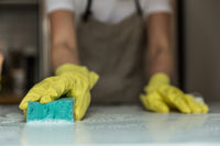 person cleaning a counter top in gloves with a green sponge