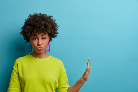 Dark-skinned woman puckering her lips, rising her hand to the side, waering pink earings, green shirt, in front of a blue wall