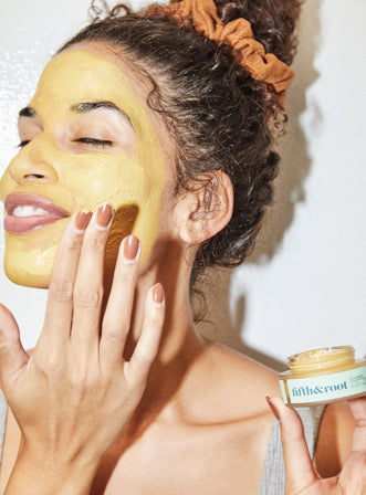 Smiling woman with curly hair tied in a bun applying Fifth & Root's creamy and yellow Moonlight Cooling Glow mask on her face