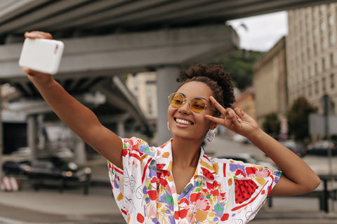 Dark skinned woman with yellow sun glasses making peace sign to her temple as she takes a selfie under a bridge