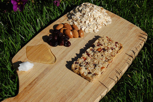 Coconut oil honey almonds cranberries oats on cutting board with granola bar